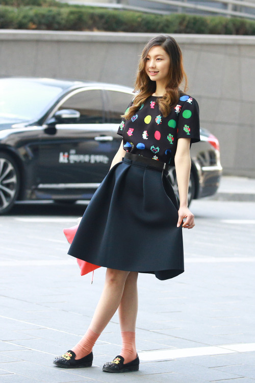 Break the elegant chic of a black A-line skirt with some cute slippers and socks and a printed tee.