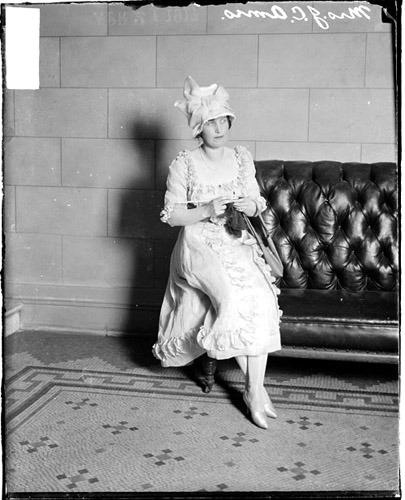 Portrait of Mrs. J. C. Ames, sitting on the arm of a leather couch in the lobby of the Auditorium Theater, located at 430 South Michigan Avenue in the Loop community area of Chicago, Illinois.1917