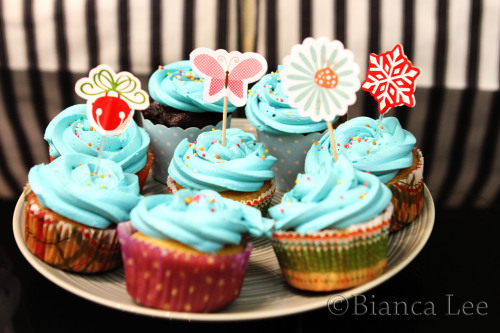 blue christmas cupcakes! chocolate and vanilla cupcakes with buttercream frosting recipe: makes 12 cupcakes 1/2c + 3/8c flour 1 cups sugar 3/8 c cocoa powder 1 tsp baking soda 1/2tsp baking powder 1tsp salt 1 c milk 1/4c oil 1 egg 1 tsp vanilla 1c hot water 180C.  Sift flour, baking powder, baking soda, salt, cocoa powder. Mix in sugar and mix until combined. Beat milk, oil, eggs, vanilla. mix in with the dry ingredients and beat until combined. Slowly add hot water and beat. It should be a pretty thin batter, but not water like consistency.  Pour in cupcake liners, Fill 3/4 full (or even less if you don't want it to rise too high) and bake for 20 minutes. Once it's done take out and let it cool. Vanilla Variation: replace cocoa powder with flour, and reduce the sugar to 3/4c Frosting: 180g butter softened 1c icing sugar 1tsp vanilla blue food colouring beat butter until creamy, sift in icing sugar and beat (you may need more, depends on how sweet you want it to be). Add vanilla and beat. Beat in a few drops of colouring. Frost and decorate cupcakes