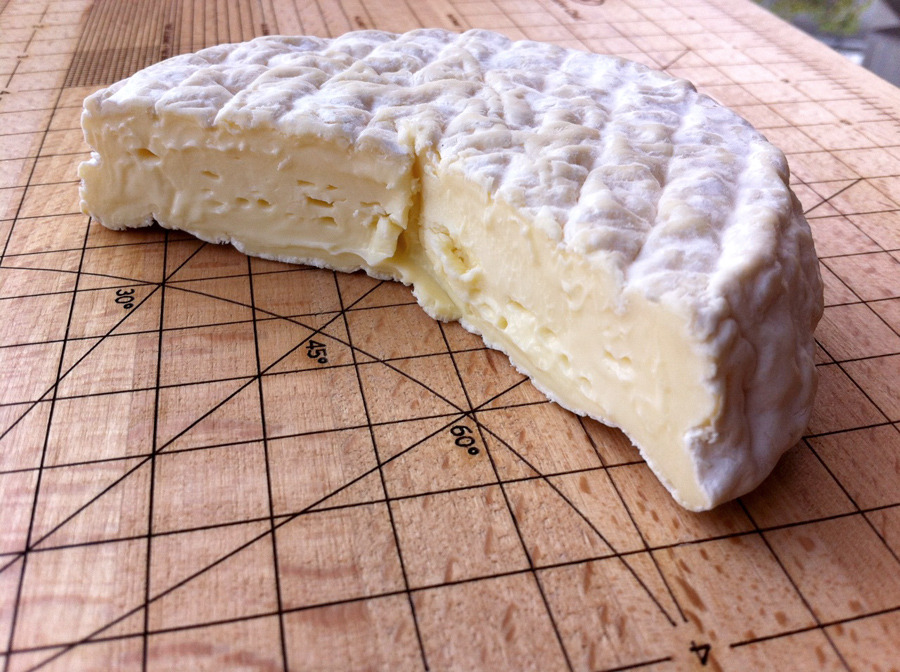 When making cheese, we often worry about things like rind development, flavor, aroma, texture, and forget about the important things, like: what are the angles, degrees, vertices of your cheese? A balanced curve is essential to the distribution of flavor, and you want the ridges in the rind to be distributed approximately 10º from each — Ok, not really. Actually, I just received an Obsessive Chef Cutting Board as an early Christmas present, and thought it would make a visually striking cheese plate for my latest batch of raw cow's milk bloomy rind. I'm pretty happy with this wheel; the rind is thinner and more delicate than past batches, and the texture of the paste is softer and higher in moisture. I've tweaked, and dialed back, the amount of rind cultures used considerably, adding less p. candidum and a bit more geothrichum. The texture is also moister and softer than past batches, with a nice creaminess as it warms. It is noticeably pungent (read: barnyardy) when first unwrapped, but that dissipates somewhat. In flavor it is mild, milky, and grassy, a little bit sour, with a subtle meatiness. I'd love to develop more of a mushroomy character, and the salt balance still needs work. But overall it feels like a solid step forward in the bloomy rind realm.  No name for this cheese yet. We'll just call it Batch G13BL-RC.