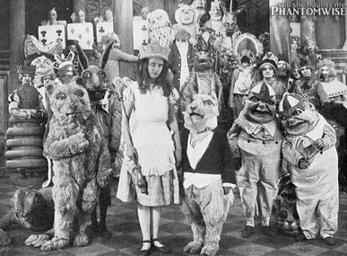 Viola Savoy as Alice, Herbert Rice as the White Rabbit, and Louis Merkle as the Dormouse with the rest of the unknown cast from Alice in Wonderland (1915)