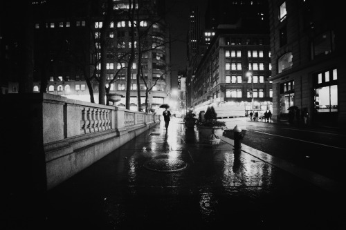 "New York City night. Rain. Bryant Park. Midtown.—-  Through eyelashes wet with rain,  a thousand thoughts fall  to the ground   and through the raindrops  the city lights blur together  as shadows make their way  into the night -   impermanence  registered with  every blink.   —-View this photo with a comment thread on my Google Plus page—-View ""New York City - Rain and Wet Sidewalks"" in my photography portfolio here, email me, or ask for help."