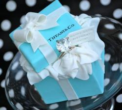 "Tiffany box cakelet (4"" square). Big fake ring supplied by my friend's mum. Tutorial for this cake in my Notes.    Just a quick tutorial for this 4"" Tiffany box mini cake, by request.  1. Make the lid at least two days in advance to allow it to dry. I thought of all the ways I could make the lid but in the end, as this was such a small cake, it seemed easiest to make a hollow lid.  2. I had a box that had a lid of exactly the right size. I've also seen gift boxes of the right in the dollar store (yes, I go there to buy rolls of shelf-liner to make a non-stick base in my cake boxes) so you should be able to pick up a box of the right size in the gift-wrap section. I use this method for larger lids too, but normally leave the cardboard lid inside.  3. Colour your fondant with a few drops of Wilton Teal gel colour until you have the shade you want. This was a quick job and I only needed to adjust the shade a little darker once. Be careful though, as the colour seems to darken and intensify once you stop kneading. Stop when the colour is lighter than you think it has to be.  4. Roll a piece of fondant large enough to cover your real box lid. Not too thin, as you want the fondant to be able to support its own weight. About 1/8"" thick is perfect.  5. Dust your real box lid with cornstarch or powdered sugar and lay your fondant over the top. It's tricky to form the shape as the fondant moves around because of the cornstarch, but persevere. Pinch the corners together and then snip them off vertically with some sharp scissors.    6. Once the corners are snipped off, you may need to smooth them down a little.  7. Trim off the excess fondant around the edges to create a neat box shape. Carefully slide a sharp knife between the fondant and the sides of the box to just ensure it's not sticking. Leave it to dry with the box still inside for as long as you can.  8"" CAKE NOTE: I used the above method for my lid and it worked perfectly. I used Wilton fondant without Tylose and used an 8"" square cake board inside the lid to support it and left it on when I added it to the finished cake. I didn't use the 'pinch and snip' method for the lid, I smoothed it as if I was covering a square cake.  Note: You can try using gumpaste for this, obviously, as long as you're able to get an exact match to the colour of the fondant you use for the cake part. I tried adding Tylose to my fondant, but it was Satin Ice and it just cracked as soon as I tried to fold it over the lid. If you're using any other brand of fondant, it might be worth a try. I don't recommend trying this with the softer fondants like Fondarific/Duff or FondX unless you can add Tylose powder to make it harden.  8. Make the now world famous Royal Bakery bow! :-) Tutorial here:  http://www.youtube.com/watch?v=-0Ptv8TAUWM  Leave the bow to dry along with the lid.  9. Tort and fill your 4"" cake. Mine was 3"" high. I used ganache to make it super-sturdy and smooth and used the upside down method that I love. Ganache was really the secret to getting the straight sides and sharp-ish edges.  http://sugarsweetcakesandtreats.blogspot.com/2010/05/covering-cake-in-ganache.html  This tutorial doesn't show you how to ganache a square cake, but the method is pretty much the same.   10. Try your hardest to ensure your cake measures 4"" at the bottom as well as the top (or whatever size you're doing)! I had do a few more sweeps with my bench scraper to get it just right. It makes getting the fondant on so much easier.  11. I rolled out my fondant for covering the sides of the cake about 1/8"" thick. I used a single strip that would wrap all the way around the sides. For this cake the fondant was 4 x 4"" = 16"" long and 3"" high (the height of my cake). I didn't bother covering the top as I knew it would be covered with fondant tissue paper later.  8"" CAKE NOTE: I used four panels of fondant for the larger cake which ran from the middle of each side, around the corner to the middle of the next side. This way, each join was covered by the ribbon and there were no edges to be seen at the corners.  12. Lightly but thoroughly moisten the ganache on your cake. Any places you miss with water or Crisco (which is what I use) are apt to form air bubbles. I either wet my hands with water and rub all over the surface, or rub with Crisco… just a very light coating. You don't want water dribbing out from under your fondant.  13. Cornstarch your strip and roll it up around a small rolling pin to allow you to transfer it to the cake and to help it to keep its shape. Make sure the bottom of the rolling pin doesn't stick out. You want the edge of your fondant to be able to touch the turntable and not the rolling pin.  Note: If you use stupid Satin Ice fondant, moisten your cake FIRST and then roll out your fondant. The longer your Satin Ice is left rolled out before applying it to the cake, the more likely it is to crack at the corners. I used Satin Ice and, because I know how horrible it is, had the stuff rolled, cut and ready to apply in about 4 seconds. :-)  14. Place the edge of your fondant strip in the middle of the back of your cake. The join will be covered with a ribbon, so this is the best place to start. Unroll your strip around the sides of the cake, pressing firmly as you go with the flat of your hand. When you reach the back again, you might have to trim some excess fondant off due to stretching as you went around. Leave this for now and concentrate on your corners first. Especially if it's Satin Ice!  15. Using a fondant smoother, smooth the sides of your box. If you have two, butt them up against each other at the corners to give you lovely sharp edges.   16. Go back and trim off any excess fondant you have at the join. This doesn't have to be neat, but don't overlap as it will show underneath the ribbon later.  17. If you have excess fondant at the top of your cake you can slice this off with a sharp blade or, if it's not too much, leave it.  18. When the fondant on the main cake is nice and dry and firm, you can apply your ribbons to the sides. The way my ribbons are laid out makes no logical sense, but my friend asked for the Tiffany logo and the bow, so the only way I was going to do that was to put the bow off-centre and the logo in the corner. But I still wanted the ribbons on the main cake to be centred, so that's how I did it. In fact, once the lid is on, it sort of all lined up, although I know it makes no sense. You're welcome to make more sense with yours!  19. Cut the ribbons from very thin fondant, about 3/4"" wide and as high as your cake. I sprayed mine with pearl lustre spray before applying to the cake, so be careful you don't transfer the sparkle to everything you touch. When applying the ribbon, make sure the bottom is flush with the bottom of the cake. This is harder than it looks and the ribbon at the back had a tiny gap that drove me crazy!  Getting the ribbons straight isn't easy, especially when I roll my fondant so thin. Can't really give you any tips, other than as soon as the ribbon is on, use the back of a knife to gently nudge it into place.  20. With any luck, a few days have passed now and you can check your lid. Fingers crossed that you can just ease the real lid out and the fondant lid should be nice and dry and stand up on its own. Replace the real lid back inside though so you have some support for the next step.  21. Now's the time to draw on the logo and discover that you have the world's shakiest hands. I measured the area I had for the writing, taking into account the position of the ribbons I would add later, and printed a logo to the right size. I used two pieces of opaque tape (check somewhere non-critical that it sticks, but not for good!) to mark out the height on my letters and to tape the printed logo to the fondant above wher you're going to write. I used this as a guide as I was writing.  22. I used a brand new edible ink pen so that I could ensure the sharpest tip possible and just went for it. Very scary and there are some dodgy letters, but it looks OK overall.  23. Now add your ribbons to the lid of the box and your super-awesome Royal Bakery bow. My bow was stupid because the swags stuck out into mid-air as I'd dried them with the bow. If you have any sense (not like me) make your swags fresh, don't leave them to dry. :-)  Note: I make my swags in advance now and freeze them on parchment paper in an airtight container until needed. Leave them to thaw for 10 minutes before you use them to avoid fingerprints.  24. I now added a layer of fondant tissue paper to the top of my box. It took about five pieces to cover all the edges. Roll out a ball of white fondant very thin and just fold and crease it carefully to make the tissue paper.  25. Now decide on the position of your lid, taking into account any rings or other jewels you might be adding. I wanted the back of my lid to be raised up slightly so the bow and logo were easily visible, so I cut a sqaure from a rice crispy treat and placed it on top of the tissue paper. This also added a bit of support to the lid. I covered it with more tissue paper. Keep adding more until you're happy with the look.  26. I attached the lid by moistening the edges and also the top of the tissue-paper covered rice crispy treat and pressing down gently. It was pretty stable.  27. I attached a little tag with a message imprinted with a little letters. I bought the kit on ebay from Malaysia. It was super-cheap. Great way of adding a message to small cake. Search Google for 'Brigitte Keks.'  That's it! Hope it useful, please ask if I can help."