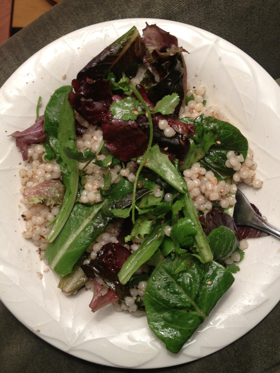ISRAELI COUSCOUS  on a bed of mixed greens with Greek dressing, capers, sesame seeds, sage, cilantro and dill seed