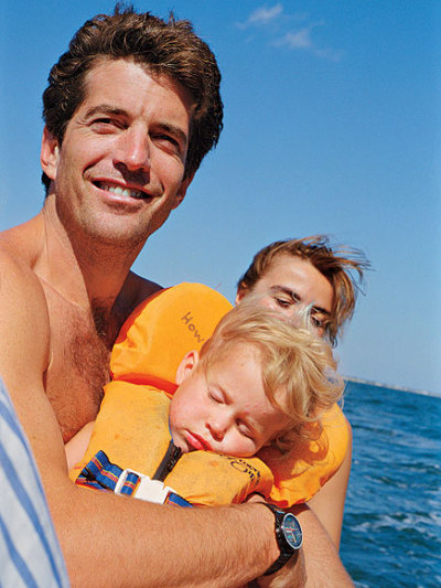 "jfkjr:   ""Olivia had fallen asleep in his arms,"" recalls Sasha of this shot taken on a Hyannis Port boat ride in 1998. ""The water got rough, and she just reached out to John. He was so proud. I think that seeing us with our children made him think, 'Yes, I can do this.' I used to say to him, 'Why do little kids follow you? Is it because you're handsome and a Kennedy?' The beauty is that kids are blind to all that. That's the expression you see there. He appreciated that."" (Photo courtesy Sasha Chermayeff)  (via people.)"