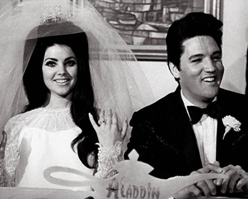 "erinkrystynax:  suplois:  Priscilla and Elvis on their wedding day, May 1, 1967.  hair goals  Friends outtakes #154: Chandler Bing travels back in time and kills elvis to wed priscella.  The ceremony has finished and the newly weds continue to exchange formalities with their friends and family. Unbeknownst to everyone at the function, let alone his future wife, Chandler Bing has completed step two and three in his 5 step plan to assume the role of the king of rock n' roll.  So far the scheme had gone on without a hitch. years of planning finally set into motion, he could not believe how perfect it has played out, every wink and gesture carefully replicated further convincing everyone of his authenticity. It was only until Chandler Bing accidentally ad-libbed one line that his scheme fell to shambles. this one line he had no intention of ever uttering. after hundreds of hours of method acting around the new york streets while his friends assume he is at 'work' trying his best to fool real people in real time rather than standing in front of a mirror and hoping for the best. this one line, the chandlerism which tore everything apart, breaking his character into an irreparable sate. as a photographer positioned herself to take the iconic photo, Mr. Bing uttered the one line he had been trying to supress since assuming his idol's role many hours before. ""could my hair be any more mistress of King Louis XV!?!""  Pictured above - Mr. Bing (as elvis) smiling sarcastically at the photographer (not pictured) mere moments before breaking character."