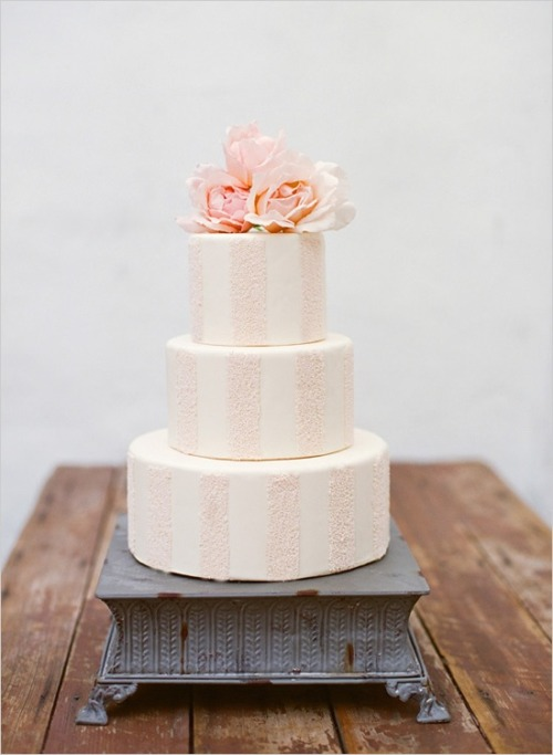 pink and white striped wedding cake with pink roses on top