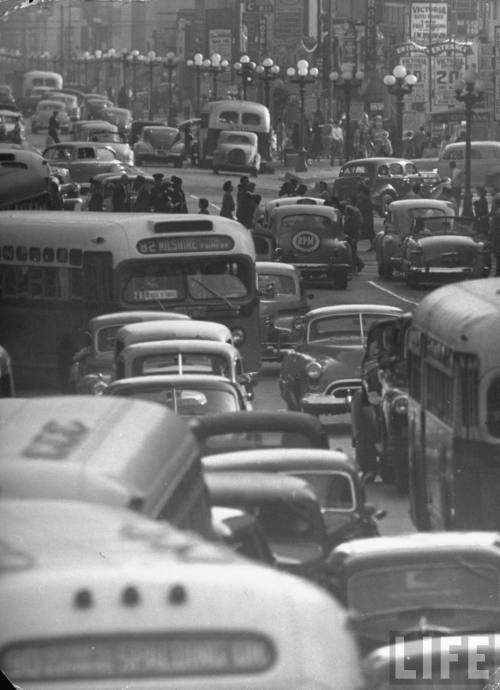 bygoneamericana:  Traveling through rush hour traffic in downtown Los Angeles, 1949. By Loomis Dean  Those street lamps aren't still there, are they? Because I can't recall a downtown boulevard with as many of this kind.