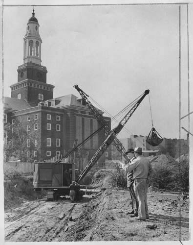 "Via Brooklyn Visual Heritage:  Constuction site at Brooklyn College, with men operating steam shovel in ditch at left; two men (one in suit) in right foreground observing construction; LaGuardia Library in background. Caption: ""New Student Center: From 1930 student population of 5,459, B. C. enrollment figures have soared to 16,514 and forced construction of further campus facilities. Construction crews are now at work on new Arts and Student Center Building that will boast 2,500-seat auditorium and house Departments of Design, Music and Speech."""