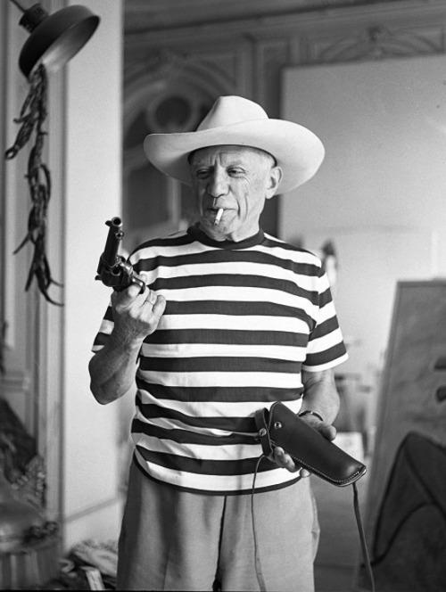 realgentlemensclub:  Pablo Picasso holding Gary Cooper's gun in 1958