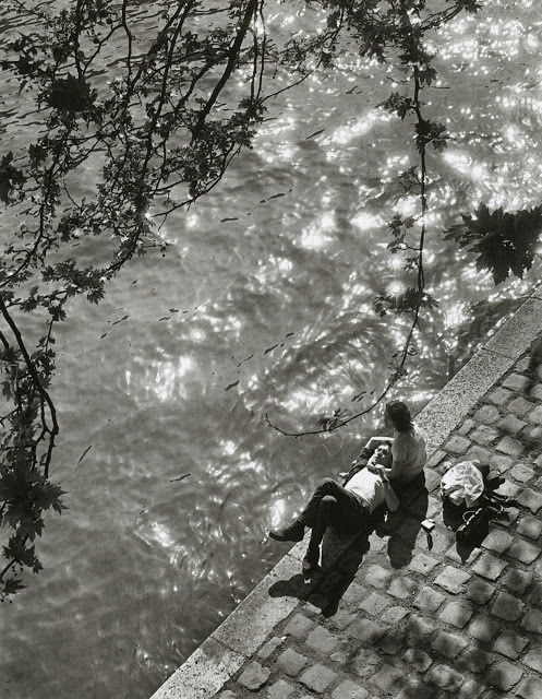 blackpicture:  Alfred Eisenstaedt A young couple enjoying lunch on the Right Bank of the Seine, just below Notre Dame. Paris (1963)
