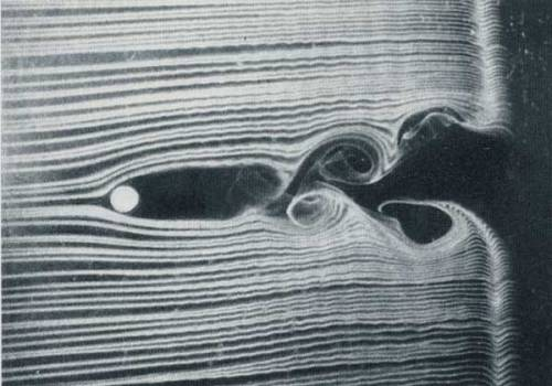 A flow visualization behind a cylinder shows the formation of a von Karman vortex street. The frequency of vortex shedding in the wake is directly related to the speed of the airflow—the higher the velocity, the faster vortices will shed from the cylinder. This relationship is expressed in the Strouhal number, which remains constant for any cylinder. (via freshphotons)