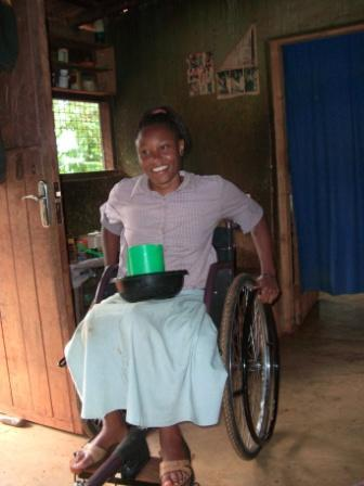 Brasilla, a KASI member who just received a new, free wheelchair, in her home.