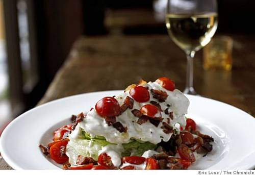 a bleu cheese wedge salad with bacon and tomatoes, and a glass of sauvignon blanc