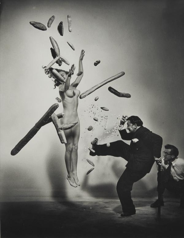 surrealism:  Popcorn Nude by Philippe Halsman Due to the popularity of this post one week ago, I found another exciting Halsman photo featuring Salvator Dalí. This one, like Dalí Atomicus, was attempted multiple times.  In fact, the first nude model grew tired from jumping, so Halsman made a substitution who eventually got it right. The bread was tossed by an assistant, Dalí threw the popcorn and kicked, the woman leapt, and magic happened.