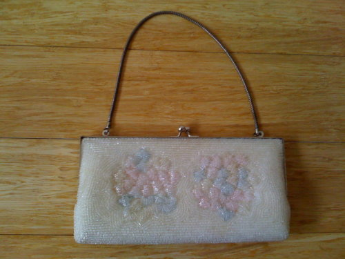 "Vintage beaded clutch. Lined with pocket. Hinge opening with chain handle. 8"" x 4"" Donation: $12"