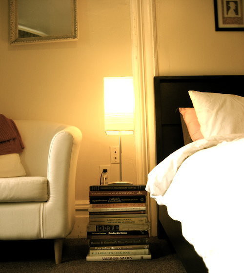 Weekend Decorating Tips from 52books: Need a bedside table? Can't find one you like on a limited budget? Choose books! Go to your local used book store and get the biggest, heaviest, most out of date books you can find. Ideally, these should not cost more than $1 each. Then, go home and stack them up. Add a lamp of your liking. The best part of this project is that if the need arises, it can teach you how to bake a pie, do business without taxes, save endangered species, and find Lithuania on a map. Can't beat it! **This DIY will make you look smarter than you are, but it does not include a drawer.