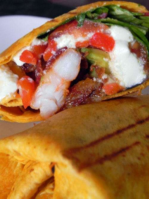 Shrimp BLT Wrap with Tabasco butter sauteed shrimp, mozzarella, bacon, roasted peppers, avocado, chili mayo and chipotle cream cheese wrapped in a sun-dried tomato tortilla from Gott Gourmet