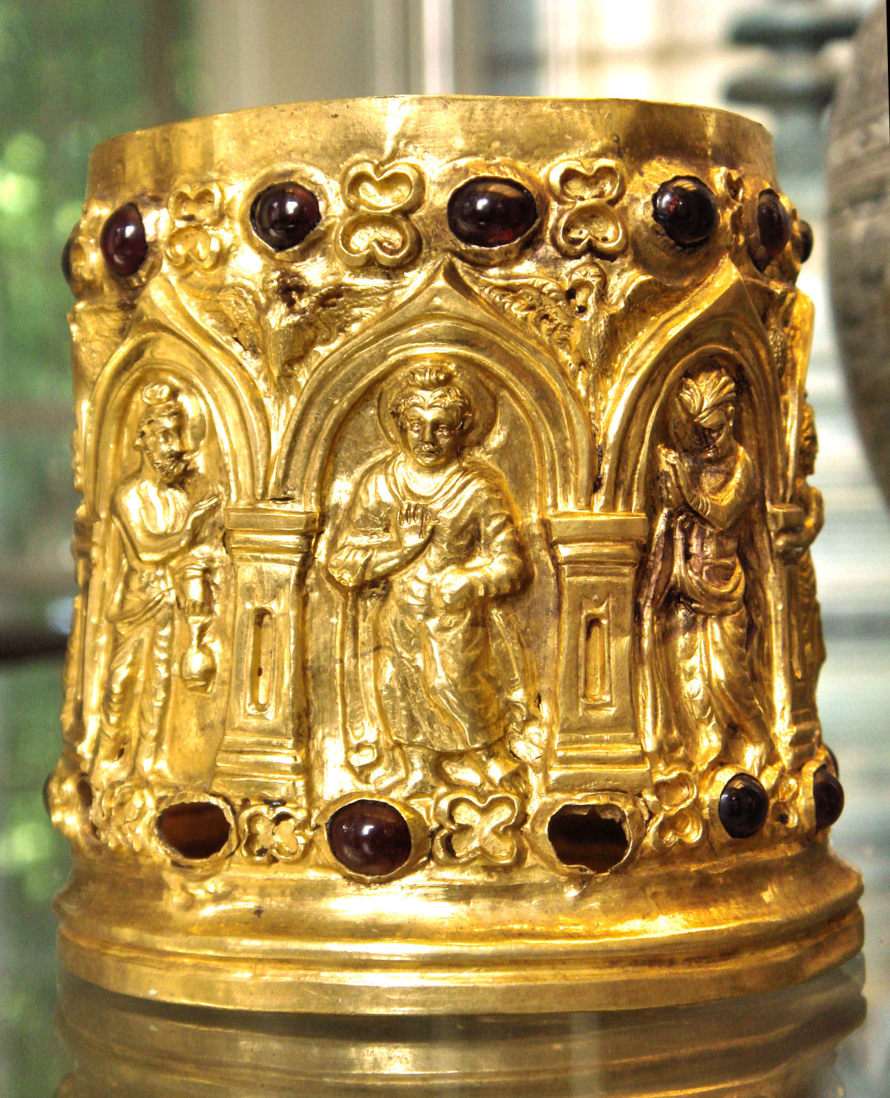"The Bimaran Reliquary. From stupa 2 at Bimaran, Gandhara (in modern Afghanistan), 1st century AD. The Bimaran Reliquary is a small gold reliquary for Buddhist relics, and shows one of the earliest depictions of Buddha from the north-west region of Gandhara. The inscription stated that the reliquary contained some of the actual ones of the Buddha (the bones, however, are missing). Instead, the relic was deposited with beads of precious stones, small burnt pearls, and four coins. Segment from the British Museum artifact statement:  The arcading round the side consists of eight pointed arches, known as caitya arches, that rest on pilasters. The compartments are divided principally into two sets of three niches. Each has a Buddha in the centre flanked by two similar deities in profile who face the Buddha.  The remaining two compartments show a figure frontally with his hands held together in a prayerful gesture of reverence, anjali-mudra. In the spandrels between the arches are eagles with outspread wings and heads turned so that they face each other. The entire frieze is sandwiched between registers of garnets that alternate with a four-lobed floral motif.  The Bimaran casket was kept in a steatite box, with the inscriptions stating that it contained some relics of the Buddha. The inscriptions on the box read: From the main body of the container:  ""Shivaraksita mumjavamdaputrasa danamuhe niyadide bhagavata sharirehi sarvabudhana puyae""  ""Sacred gift of Shivaraksita, son of Munjavamda; presented for Lord's relics, in honour of all Buddhas""  And from the lid of the container:  ""Shivaraksita mumjavamdaputrasa danamuhe bhagavata sharirehi""  ""Gift of Shivaraksita, son of Munjavamda; presented for Lord's relics""  This reliquary is a crucial object for the history of Buddhism, the development of the Buddha image on Buddhist art, and the best preserved example of early Indian goldsmithing. Courtesy & currently located at the British Museum, London. Photo taken by World Imaging"