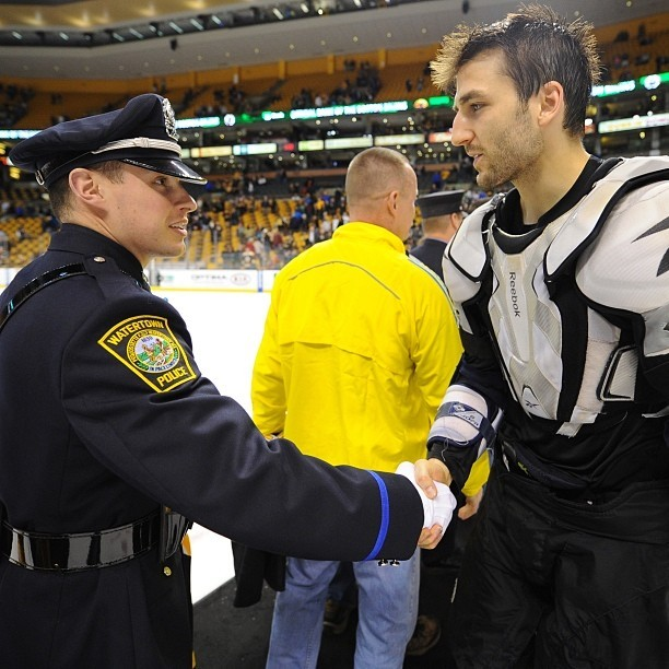 nhlbruins:  Patrice Bergeron and a Watertown PD first responder shake hands during Shirts Off Their Backs #nhlbruins