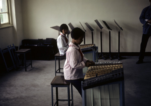 Two girls in a music room, playing yangqins, a dulcimer-like instrument, at the Children's Palace, Shanghai, China. 1979