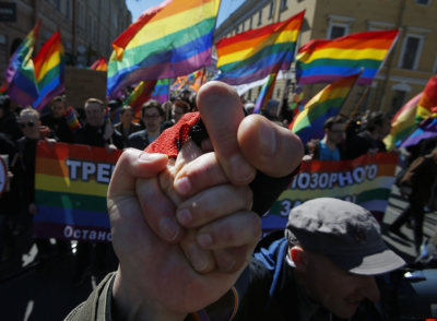 "Gay rights activists clasp hands as they march during a tradition May Day rally in St. Petersburg, Russia, Wednesday, May 1, 2013. The poster reads, ""We demand the abolition of the homophobic law!""  Photo: AP / Dmitry Lovetsky"