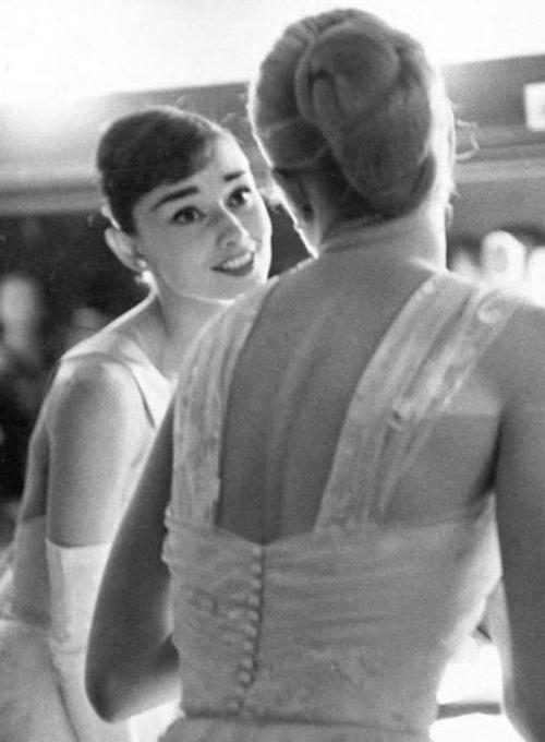 Audrey Hepburn with Grace Kelly backstage at the Academy Awards photographed by Allan Grant, March 21, 1956.