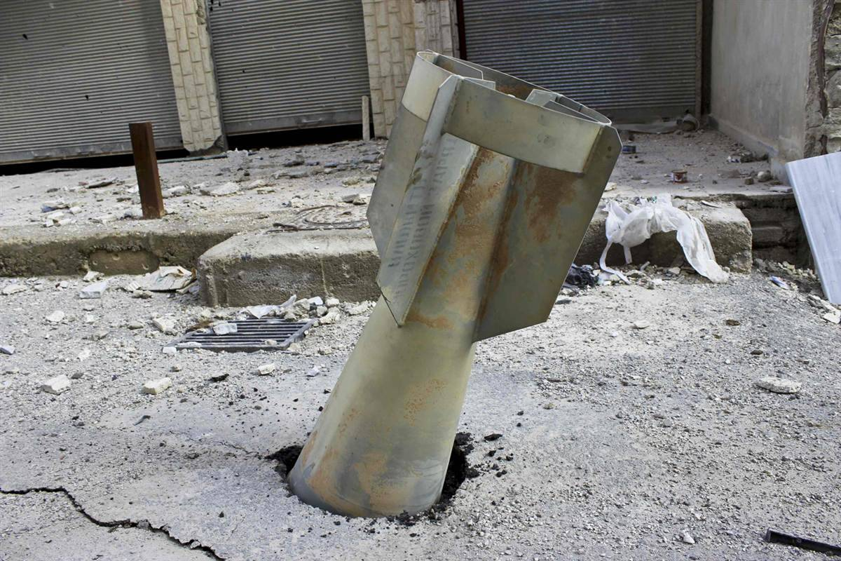 politics-war:  An unexploded bomb is lodged in the street in the Ain Terma area in Ghouta, east of Damascus.