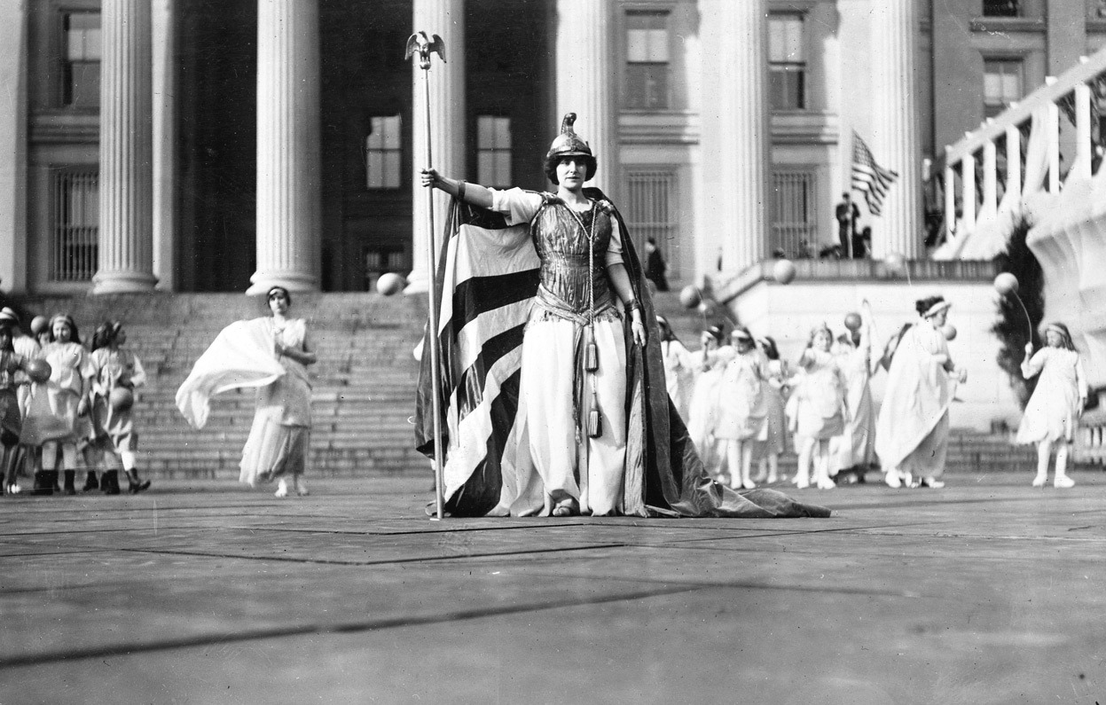 "From 100 Years Ago, The 1913 Women's Suffrage Parade, one of 24 photos. Here, German actress Hedwig Reicher wears the costume of ""Columbia"" with other suffrage pageant participants standing in background in front of the Treasury Building in Washington, D.C., on March 3, 1913. The performance was part of the larger Suffrage Parade of 1913. (Library of Congress)"