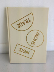 "(sign) [show] {trade} Thomas Macker  88 pages, 12 page essay, 39 images SIZE: 7 x 10"" Book Cloth Cover w/ gold foil stamp 70# uncoated white and 100# Satin white  ISBN 978-0-615-76630-0 Text by Arjuna Neuma Designed by Women Typeset in LLBrown and MSPGothic     First Edition, 500 copies Copyright © 2013 in the pines books Printed in the United States of America   Published in conjunction with an exhibition at Gallery KM Book launch details - https://www.facebook.com/events/435441186532617/?ref=3 Publisher's/Exhibition Description: Gallery km presents Thomas Macker's (sign) [show] {trade}, an exhibition utilizing photography and sculptural objects to explore the intersection between natural ecosystems and built communities, and the way in which the impulse towards constant modification –and its resulting toxicities—obfuscates our ability to connect, while magnifying our desire for that connection. The exhibition will take place from February 9th through March 16th, with a reception for the artist on Saturday, February 9th, from 6-8pm, and precedes the publication of an artist book by Macker featuring the same series of works. This is Macker's first solo show with gallery km. Conceptually, the exhibition is structured horizontally, with two formally similar series of photographic works bridged by photographs and sculptural objects that offer a dialogic counterpoint to the main series.  The first group of photographs focuses around seed signs and sacks advertising distinct crop strains of genetically modified corn and soy. The individual sacks and signs are set up at the center of still life compositions, staged in the basement of Macker's home in Jackson Hole, Wyoming.  The sacks hang from the fiberglass insulation and wooden boards of the basement ceiling, while the signs are placed in gravel on the floor. The backdrops, often constructed by hanging used textiles against the gold-painted walls of the basement, offer glimpses of American nostalgia—old quilts featuring Winnie The Pooh, The Transformers, and Disney Princesses, along with faded floral sheets, tie-dye hangings, penguins. The series is presented as a calendar of images; each photograph is named for a month of the year, with an additional one for each season. The repetition in the photographs acts as a meditation on the ways we mark time, while the content of the images posits company branding as a primary signifier of cultural and personal identity: nostalgia and desire for meaning coopted by companies that alter the foundation of our sustenance. In Macker's work, the 'seed'—as altered commodity—locates the collision between the idea of the natural world as something outside and other than human, and the natural world as what we are (as animals who eat food grown from seeds, eat animals who have eaten plants grown from seeds, breathe air full of oxygen created by photosynthesis, and on and on). This space of collision and contradiction is where Macker argues we reside, and the photographic and sculptural pieces that bridge the two still life series in the exhibition offer a glimpse of the effects of that lived contradiction.Dog God 