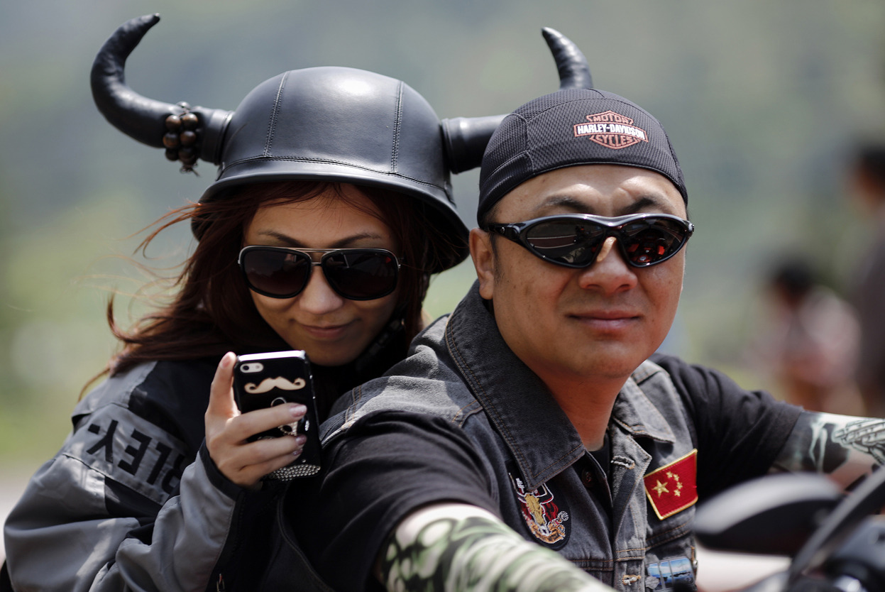 From Harley Davidson National Rally in China, one of 18 photos. A couple rides a Harley Davidson motorcycle during the annual Harley Davidson National Rally in Qian Dao Lake, in Zhejiang Province, China, on May 11, 2013. Around 1,000 Harley Davidson enthusiasts from all over China met at the rally, as part of the company's 110-year anniversary. (Reuters/Carlos Barria)