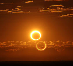 "shortformblog:  breakingnews:  'Ring of Fire' eclipse wows Australia AP: Skygazers across the Australian Outback were among the lucky few to witness a solar eclipse on Friday as the moon glided between Earth and the sun, blocking everything but a dazzling ring of light. The celestial spectacle, known as a ""ring of fire"" eclipse, was the second solar eclipse visible from northern Australia in six months. In November, a total solar eclipse plunged the country's northeast into darkness, delighting astronomers and tourists who flocked to the region from across the globe to witness it. Photo: Friday's annular solar eclipse blazes like a ring of fire after sunrise, 45 miles (70 kilometers) south of Newman, Australia. The ""second sun"" is a lens effect. (Nicole Hollenbeck via SpaceWeather.com)  Just, wow. Okay. Consider us suitably awed, sun and moon. Put something together like this and there's always room for you on our humble internet weblogs.  Gorgeous shot."