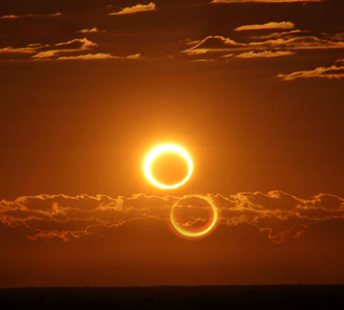 "breakingnews:  'Ring of Fire' eclipse wows Australia AP: Skygazers across the Australian Outback were among the lucky few to witness a solar eclipse on Friday as the moon glided between Earth and the sun, blocking everything but a dazzling ring of light. The celestial spectacle, known as a ""ring of fire"" eclipse, was the second solar eclipse visible from northern Australia in six months. In November, a total solar eclipse plunged the country's northeast into darkness, delighting astronomers and tourists who flocked to the region from across the globe to witness it. Photo: Friday's annular solar eclipse blazes like a ring of fire after sunrise, 45 miles (70 kilometers) south of Newman, Australia. The ""second sun"" is a lens effect. (Nicole Hollenbeck via SpaceWeather.com)"
