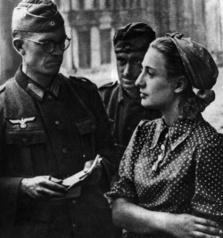 A Russian woman stares straight ahead, refusing to answer a German soldier, 1941. Getty