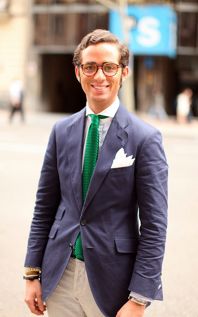 A classic navy suit punched up with a green knit tie