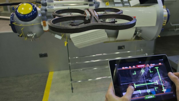"A free ESA app released today turns a popular iPhone-controlled 'home drone' into a spacecraft. The augmented reality game lets owners of Parrot AR.Drone quadcopters attempt dockings with a simulated International Space Station while flying their drones for real – in the process helping to improve robotic rendezvous methods. This new AstroDrone app is part of a scientific crowdsourcing project by ESA's Advanced Concepts Team, gathering data to teach robots to navigate their environments. ""People intuitively assess their position and motion in relation to their surroundings in various ways, based on what they see before them,"" explained team research fellow Guido de Croon. ""This new app lets us crowdsource examples of this process in practice, as a first step to reproducing it with artificial intelligence. AstroDrone Access the video ""For ESA, the result could be much more autonomous spacecraft that can reliably manoeuvre, dock or land themselves."" (via Smartphone app turns home drone into spacecraft / Technology / Our Activities / ESA) iTunes Link"