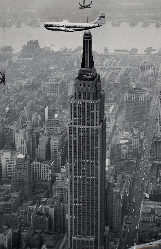 With the Empire State Building below, Pan Am's Clipper, the world's largest and fastest commercial airliner, takes a preview flight over Manhattan, 1949.