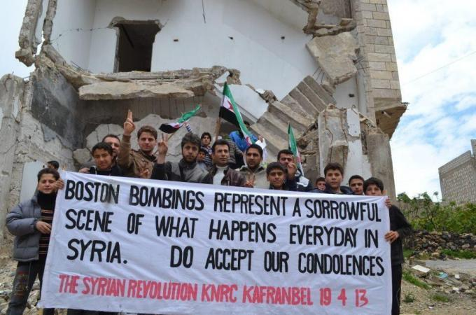"simply-war:  Syrians show their support for Boston by holding up a banner reading ""Boston bombings represent a sorrowful scene of what happens everyday in Syria. ""Do accept our condolences."""