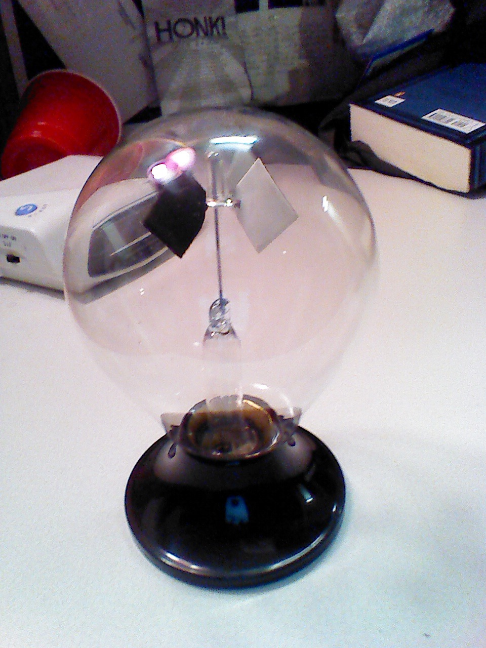 normalmodes:  Here's a cool toy. This radiometer spins when exposed to a light source. It's tempting to think that photons are imparting the spinning force on the vane directly. Photons do exert force - though massless, they have intrinsic momentum - but that radiation pressure is far too weak to move something like this. What's really happening: the black panels absorb energy from the incident light and heat up. The gas (air I presume) molecules knocking about actually kick off from those panels more strongly due to this heat. The vane thus turns only in then direction of the white panels, which absorb much less energy and thus transfer less to colliding particles. It is the kinetic force of the air particles responsible, not the electromagnetic force of the photons. I'll post a video when I get the chance!