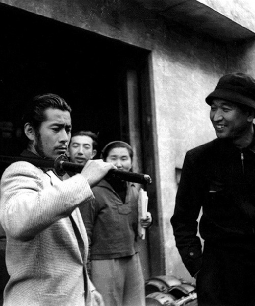 toshiro-mifune:  Toshirō Mifune on the set of Seven Samurai with director Akira Kurosawa carrying a live blade the only type of sword he would use in his enactment as samurai in films. He would often  repeat:  By carrying a live blade, it has forced me to master each movement. I must be a perfectionist. It also gives me a sense of realism.