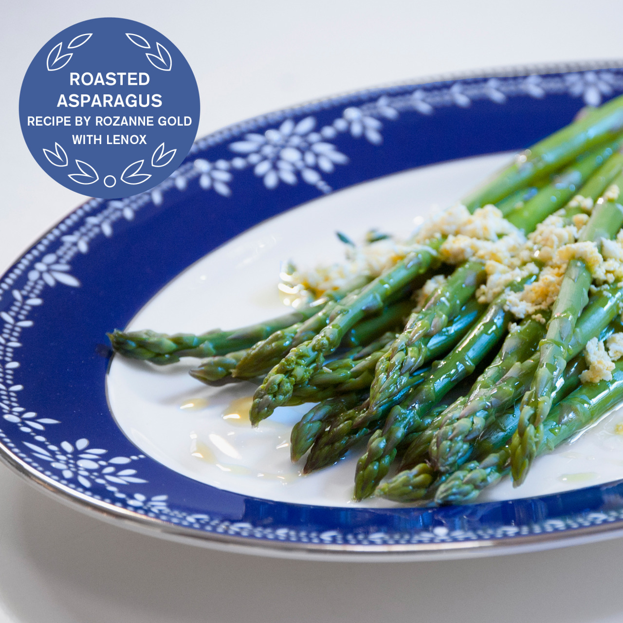 LENOX PASSOVER 2013 ROASTED ASPARAGUS WITH FRESH THYME  by Rozanne Gold Roasting asparagus at a high temperature caramelizes their natural sugars and develops their grassy flavor.  I love the simple melding of flavors – fresh thyme, and garlic, bound together with chopped egg.  - 2 pounds asparagus - 1 medium clove garlic - 3 tablespoons extra-virgin olive oil, plus more for drizzling - 1 bunch fresh thyme - 2 hard-boiled eggs Preheat oven to 475 degrees.  Finely chop garlic and add to olive oil.  Trim asparagus and place in a large bowl.  Add garlic oil, 1 teaspoon kosher salt and pepper and toss well.  Place asparagus on rimmed baking sheet.  Scatter half the fresh thyme sprigs over and around the asparagus.    Roast 10 minutes, shaking pan once or twice, until tender (do not overcook.)   Transfer asparagus to a warm platter.  Chop eggs very fine and scatter over asparagus. Drizzle with additional olive and garnish with fresh thyme.     SERVES 8 Featured Product: Marchesa Empire Pearl Indigo Oval Platter (#826276A) Lenox