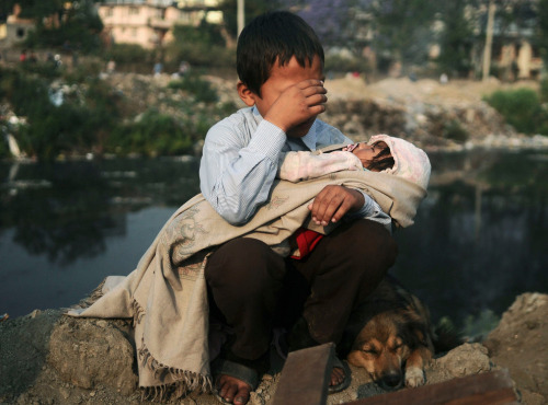 A boy in Nepal being evicted from his home. This young boy cries as he holds his sister in his lap after a confrontation with squatters and police personnel in Kathmandu, Nepal.  Ahh, God… Send me to Nepal to help these kids! This boy has to be a parent at such a young age. What are you going to do with him? Give him hope and strength, Lord… give him love!