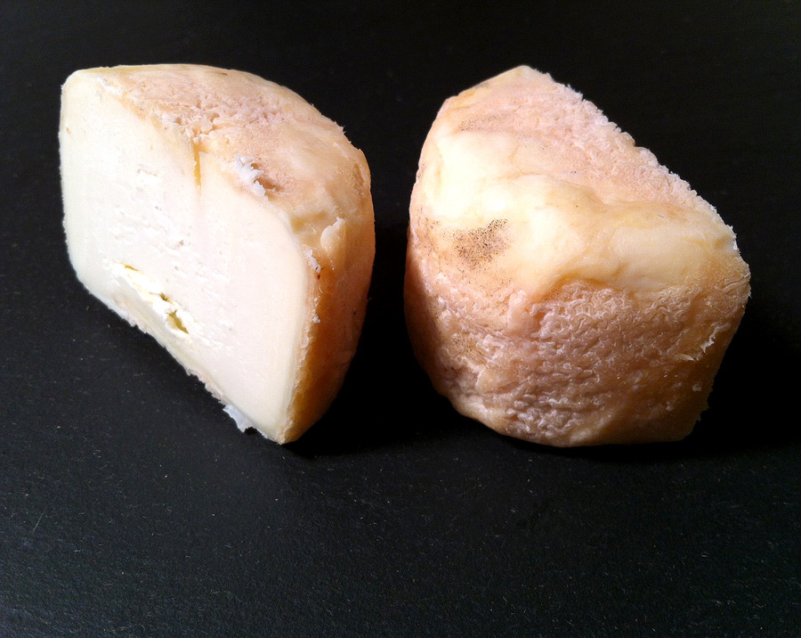 "This little crottin resembles some of the classic goat's milk cheeses of the Loire Valley, but actually hails from Kempense Geitenkaas, a creamery in Lichtaart, Belgium, north of Antwerp in the region of Flanders. Paul D'Haene and Veerle Minsaer have been making cheese since 1979, focusing on goat, in country that is known almost exclusively for its cow's milk cheeses (the trappist style cheeses being the best known, such as the Le Charmoix, recently reviewed). Paul even says that ""the goat is the cow of the poor farmer"", but there's nothing impoverished about the cheeses that he's making with their milk.  The aged 5oz crottin has a textured, stony amber exterior, opening to reveal a chalky white interior, the paste creamy and fudgy with a bit more proteolysis at the rind. The aroma is yeasty and fruity; the flavor is milky and bright with citrus notes and a distinct sour, tangy, overtone.  Purchased at Formaggio Essex."