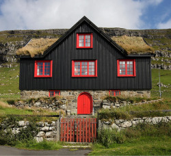 fourteen:  Black house, red windows, grass roof by frisk_gallery on Flickr.