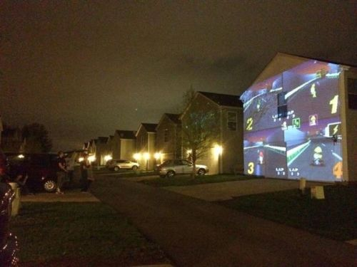 heartlessdivine:  whiskey-neat:  My friend just rigged it so she and her friends could play Mario Kart on the side of a house for someone's birthday.  Now the whole neighborhood can watch as a friendship is blown away by a blue turtle shell