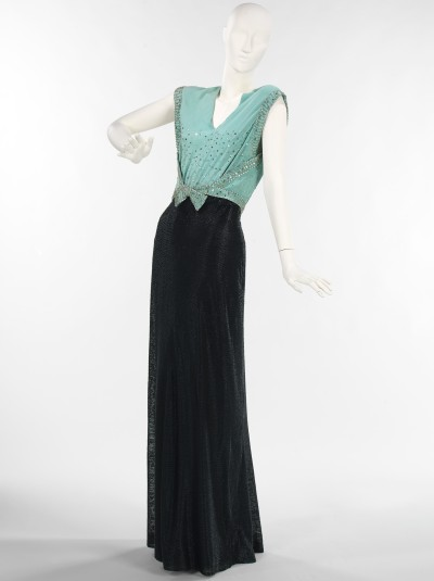 fashioninhistory:  Evening Dress 1932 After the Stock Market Crash of 1929, the era of the flapper was put to rest, the hemlines dropped and the waistline rose. A slim figure was still in vogue but this was accented by the bias-cut dress, low backs, and deep V-necks at front. The 1930s was full of glamour and with the growing popularity of the cinema, women turned to their favorite actresses for wardrobe inspiration. This evening dress evokes the idea of a chic evening. The bodice construction is inventive and daring, with its low cut and knot at front. The skirt itself is a tour de force of beadwork and would catch the light when in movement, enhancing its visual appeal.- The Metropolitan Museum of Art