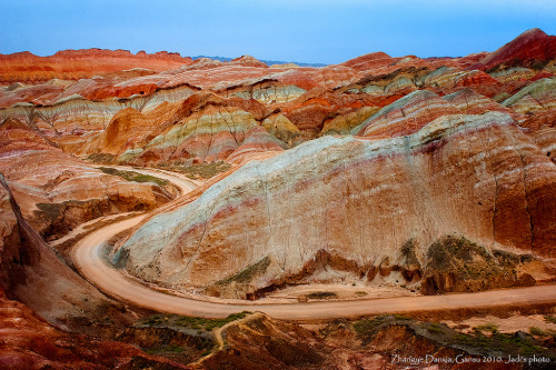 Zhangye Danxia - Geology From a Storybook Long ago, colorful sediments were deposited in western China, layer after layer, century after century. If you were there at the time, you would have seen unremarkable ground, a single hue of dirt no different from a thousand other places on Earth.  But after thousands and thousands of years subject to the forces of pressure and tectonic movement, the total of those layers has been pushed upward, letting us peek at a rainbow-hued slice of Earth's past perhaps unmatched on this planet. The planet looks more like the cross-section of a jawbreaker candy than layers of rock in these photos, near Zhangye, China. The Zhangye formation, not to be confused with this danxia, a UNESCO heritage site, reminds us how our crust is heaved and hurled throughout the ages, a slow evolution that will continue into the distant future. It's yet another story of Earth's past, written in stone, but perhaps with the same pen as a fantasy storybook. Check out more photos from Flickr user Melinda ^..^, and take some time to tour the formation in Google Earth.