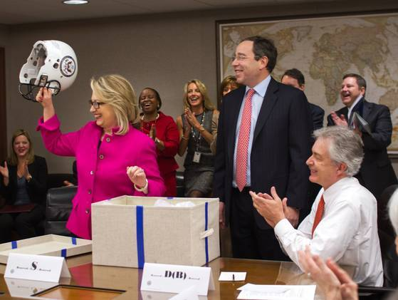 Hillary Clinton back at work — her colleagues at the State Department gifted her with a football helmet and jersey. [Photo by AP via USA Today]