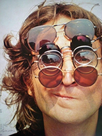 lomographicsociety:  John Lennon Smirking for a Close-Up Shot while Wearing Several Glasses One pair of sunglasses seems to be not enough to keep Mr. Lennon from squinting his eyes shut on a bright, sunny day.