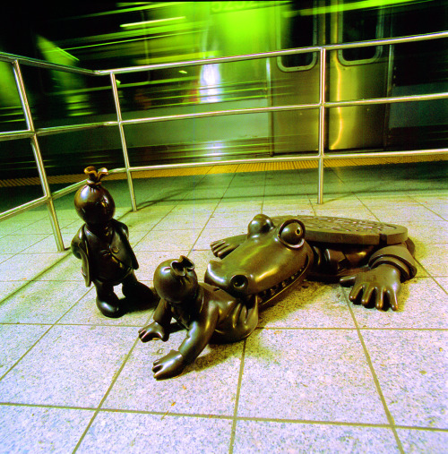 The scores of figures created by Tom Otterness to Life Underground invigorate and transform the transit environment into a place of joy and whimsy. Otterness placed his creations in unexpected places - beneath stairs and pillars, hanging from the ceiling, and on benches and railings - to surprise and delight riders as they discover these humorous and captivating inhabitants. See the bronze sculpture on railings, beams and columns throughout the 14th and 8th Avenue station!     Above: Tom Otterness, Life Underground, 2001.